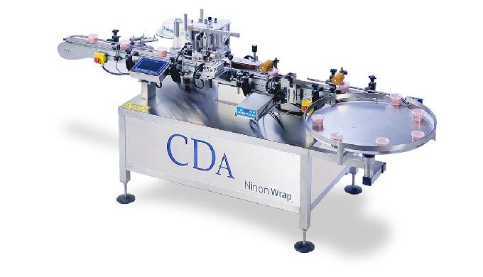 Conçue par la société CDA, la Ninon Wrap est une étiqueteuse automatique idéale pour l'étiquetage des produits cylindriq