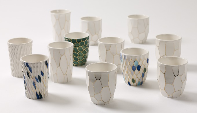 A gold line was drawn on a hand-crafted, unformatted porcelain cup. The unique glazed colors such as emerald, blue and w