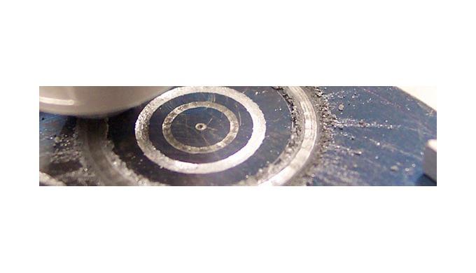 El equipo consiste en un disco giratorio sobre el que se coloca uno de los materiales bajo ensayo y que es cargado a tra