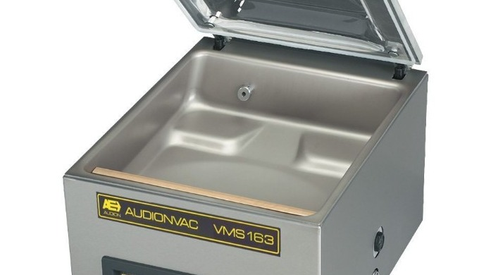 The Audionvac VMS 163 is a large table top vacuum chamber machine. This model features a stainless steel chamber with a
